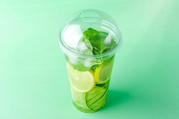 Bevanda disintossicante con cetriolo e limone in un bicchiere di plastica su sfondo verde chiaro