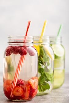 Acqua detox in tre barattoli con lamponi, limone, lime e menta
