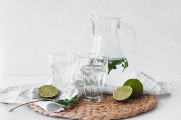 Acqua detox con frutti di lime e foglie di menta.