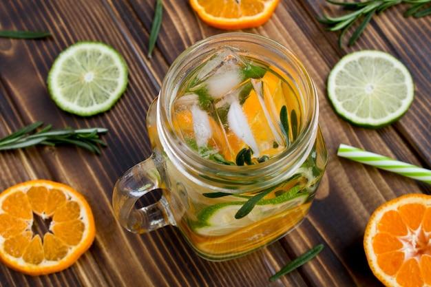 Acqua detox con mandarini, lime e rosmarino sulla superficie in legno marrone.vista dall'alto.