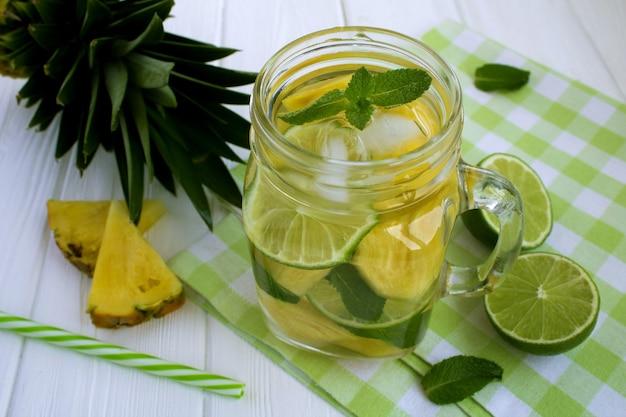 Acqua detox con ananas e lime sul tovagliolo verde