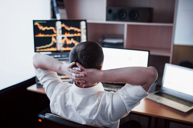 Sviluppare nuovi approcci. retrovisione del giovane in abbigliamento casual che tiene la mano sulla parte posteriore della testa e che lavora mentre sedendosi allo scrittorio in ufficio creativo