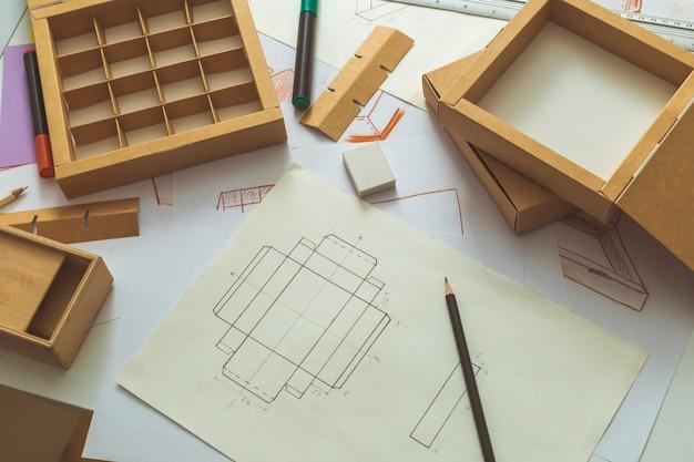 Progettazione di sviluppo disegno imballo. desktop di una persona creativa che fa scatole di cartone.