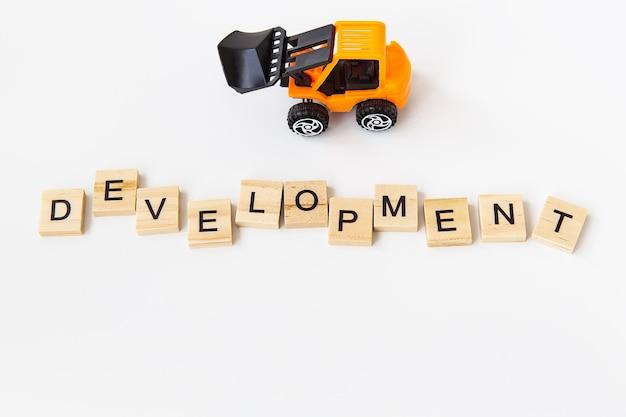 Sviluppo della parola scritta su un blocco di legno, sviluppo della scritta, piccolo trattore giocattolo. il concetto di linea, rinnovamento, sviluppo.