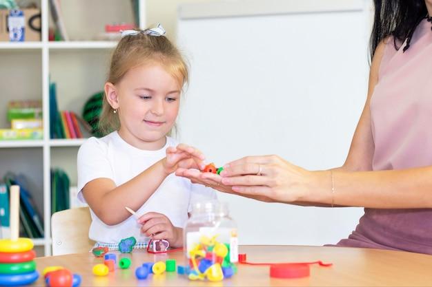 Lezioni di sviluppo e logopedia con una bambina. esercizi di logopedia e giochi con perline. la ragazza ha delle perle tra le mani
