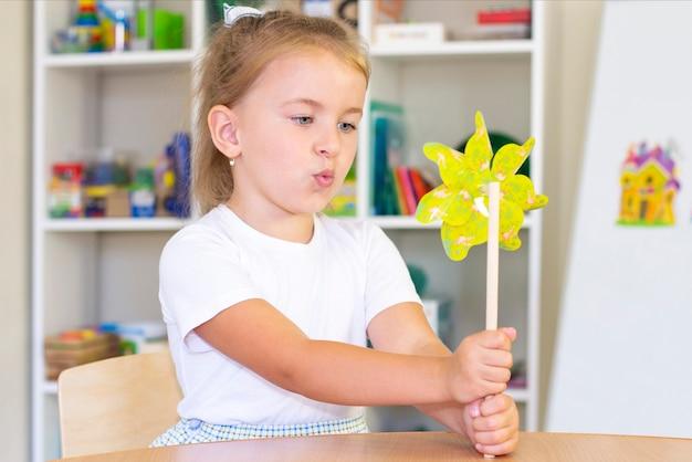 Lezioni di sviluppo e logopedia con una bambina. logopedia e giochi di spinning. ragazza che soffia