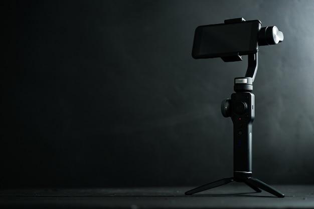 Un dispositivo per la stabilizzazione dell'immagine quando si scattano foto e video su uno smartphone su sfondo nero