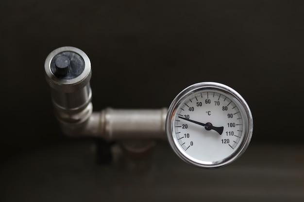 Un dispositivo per misurare la temperatura dell'acqua nell'impianto di riscaldamento. valvola limitatrice di pressione del tubo. foto di alta qualità