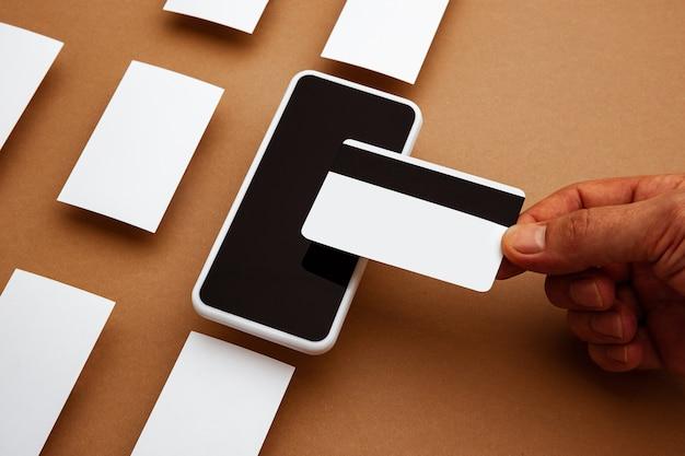 Dispositivo con schermo vuoto fluttuante sopra sfondo marrone. telefono e carte. mockup moderno e in stile ufficio per pubblicità, immagini o testo. copyspace bianco vuoto per il concetto di design, affari e finanza.