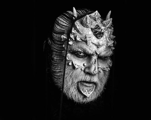 Uomo del diavolo con trucco immaginario. demone con sciarpa sulla testa isolata sul nero. mostro con occhi bianchi e spine sul viso. alieno con pelle di drago e barba grigia.