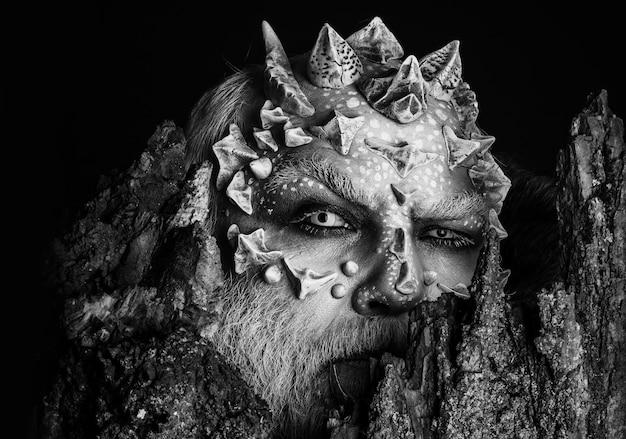 Diavolo dietro la vecchia corteccia. uomo con pelle di drago e viso barbuto. mostro con spine affilate e verruche. spirito dell'albero e concetto di fantasia.