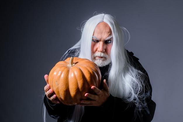 Diavolo vampiro uomo con zucca arancione bel demone con jack o lantern felice mago malvagio di halloween