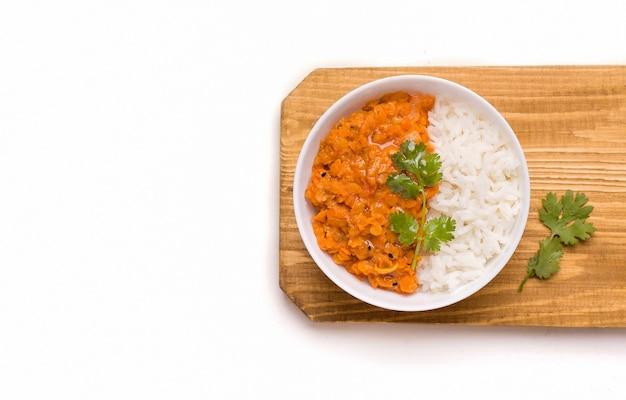 Dhal indiano vegetariano piccante zuppa di fagioli di lenticchie rosse bollite in una ciotola su bianco