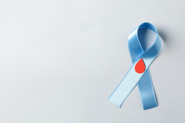 Diabete. nastro blu consapevolezza con goccia di sangue decorata