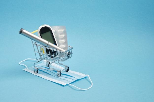 Concetto di diabete. forniture per diabetici nel carrello del negozio, pillole, glucometro, penna per siringa da insulina su sfondo blu