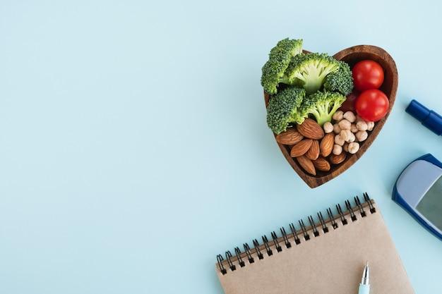 Concetto di diabete. piatto a forma di cuore con cibo sano, glucometro digitale e blocco note