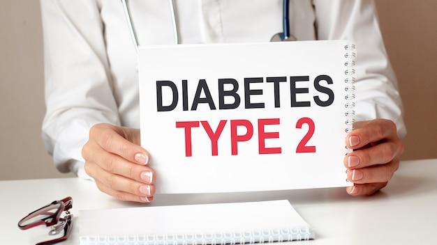 Diabete tipo 2 card nelle mani del medico. il medico passa un foglio di carta con testo diabete tipo 2, concetto medico.