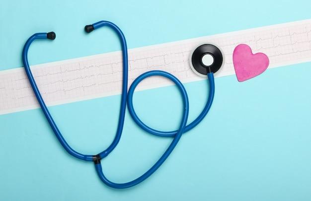 Diagnosi e prevenzione (trattamento) delle malattie cardiovascolari. cardiogramma del cuore, stetoscopio su sfondo blu. cuore sano. vista dall'alto