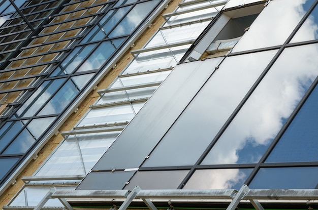 Primo piano diagonale della facciata della costruzione di vetro nell'ambito del processo di costruzione o del rinnovamento