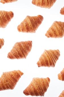 Modello diagonale con croissant fatti in casa gourmet appena sfornati su uno sfondo bianco. colazione continentale.