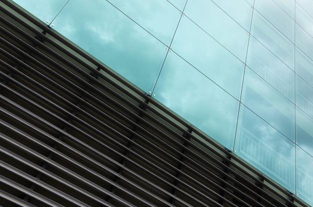 Vista diagonale della superficie della parete moderna, vetro e struttura in metallo con la riflessione del cielo.