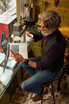 Comporre un numero. uomo serio barbuto seduto al tavolino del bar con una tazza di caffè in mano e andando a fare una telefonata.