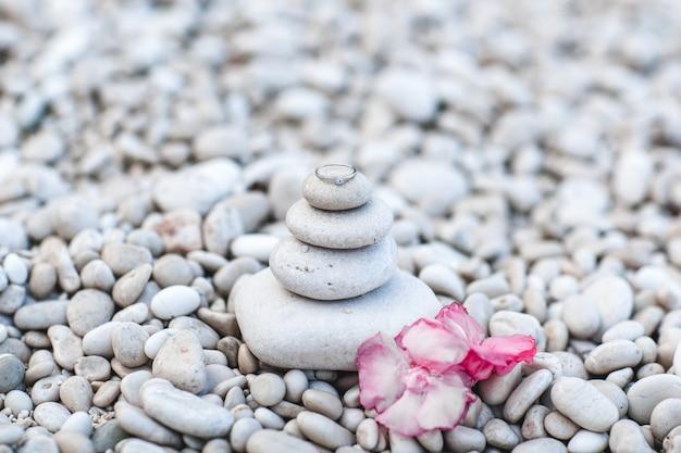 Anello di fidanzamento con diamante posto su una piramide di pietre bianche