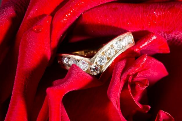 Anello di fidanzamento con diamante con un percorso di diamanti e una rosa rossa. il concetto è un'offerta per diventare mia moglie