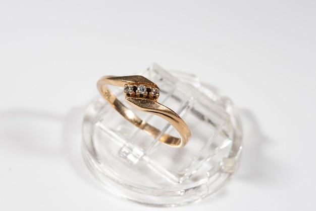 Anello di diamanti. anello di diamanti su sfondo bianco. anello con tre diamanti. fedi nuziali dorate. giallo oro.