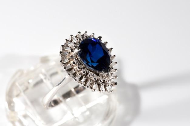 Anello di diamanti. anello di diamanti con zaffiro su sfondo bianco. anello con diamanti e grande zaffiro. fedi nuziali dorate.
