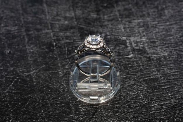Anello di diamanti, anello in oro con diamanti naturali su sfondo scuro, pietre preziose