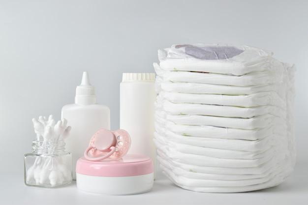 Pannolini e prodotti per l'igiene in un sacchetto di carta su sfondo chiaro. mutandine per neonati usa e getta.