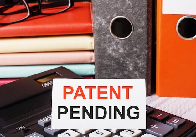 Accanto ai diari e alle cartelle con i documenti sulla calcolatrice c'è un cartoncino bianco con la scritta patent pending