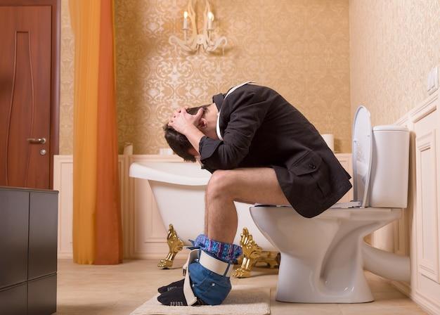 Concetto di problema di diarrea o costipazione. uomo con i pantaloni abbassati seduto sulla tazza del water