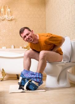 Concetto di problema di diarrea. uomo con i pantaloni abbassati seduto sulla tazza del water