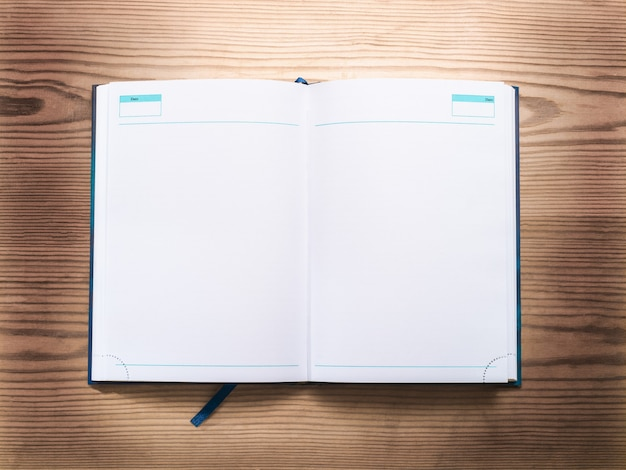 Il diario per appunti giace aperto su uno sfondo di legno piatto, vista dall'alto