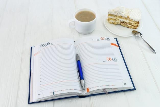 Diario con una tazza di caffè e un pezzo di torta