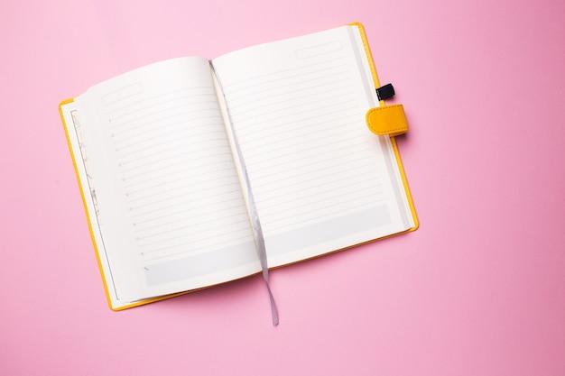 Diario con pagine bianche aperte su una superficie rosa