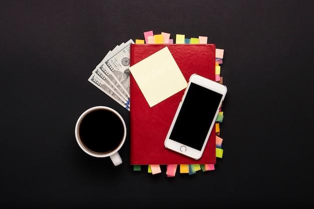 Diario con adesivi sulle pagine, tazza di caffè, banconote da cento dollari, telefono bianco, sfondo nero. concetto di business di successo, corretta pianificazione, gestione del tempo. vista piana, vista dall'alto