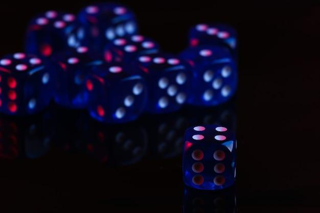 Dadi su sfondo nero con luce al neon blu rossa Foto Premium