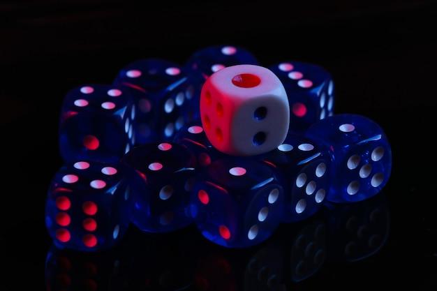 Dadi su sfondo nero con luce al neon blu rossa