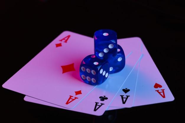 Dadi e quattro assi su sfondo nero con luce al neon blu-rossa
