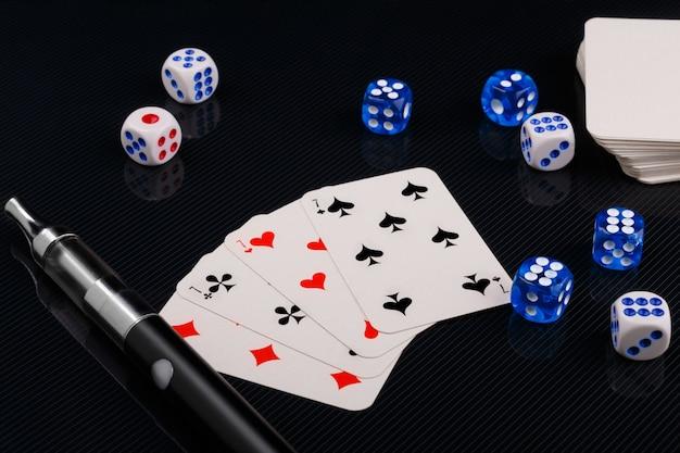 Dadi e carte da gioco accanto a un dispositivo di svapo