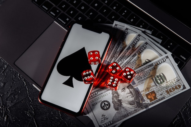 Dadi, smartphone e banconote in dollari sulla tastiera. casinò online e concetto di gioco d'azzardo.