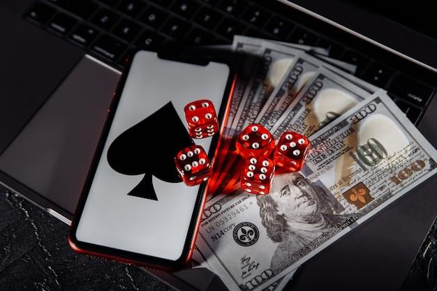 Dadi, smartphone e banconote in dollari sulla tastiera. concetto di gioco d'azzardo online