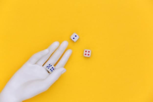 Dadi in una mano di manichino bianco su sfondo giallo. vista dall'alto