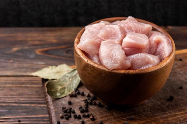 Petto di pollo crudo a dadini o filetti su fondo di legno scuro.