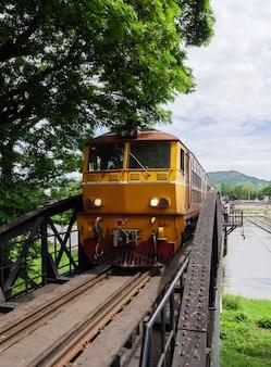 La locomotiva diesel-elettrica del treno locale sta guidando con attenzione attraverso il vecchio ponte d'acciaio