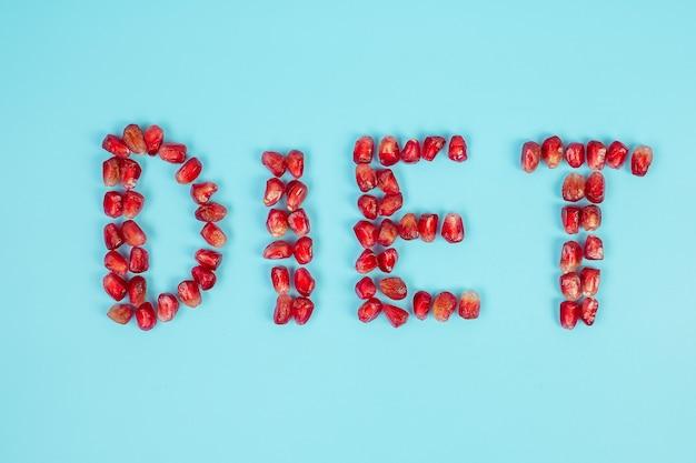 Disposizione dieta di frutta semi di melograno su sfondo blu