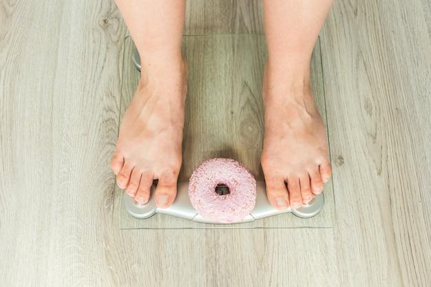 Concetto di dieta. primo piano dei piedi della donna sulla bilancia con ciambella. concetto di dolci, cibo spazzatura malsano e obesità.